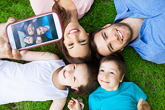 family lying on the grass face up and smiling for a phone camera